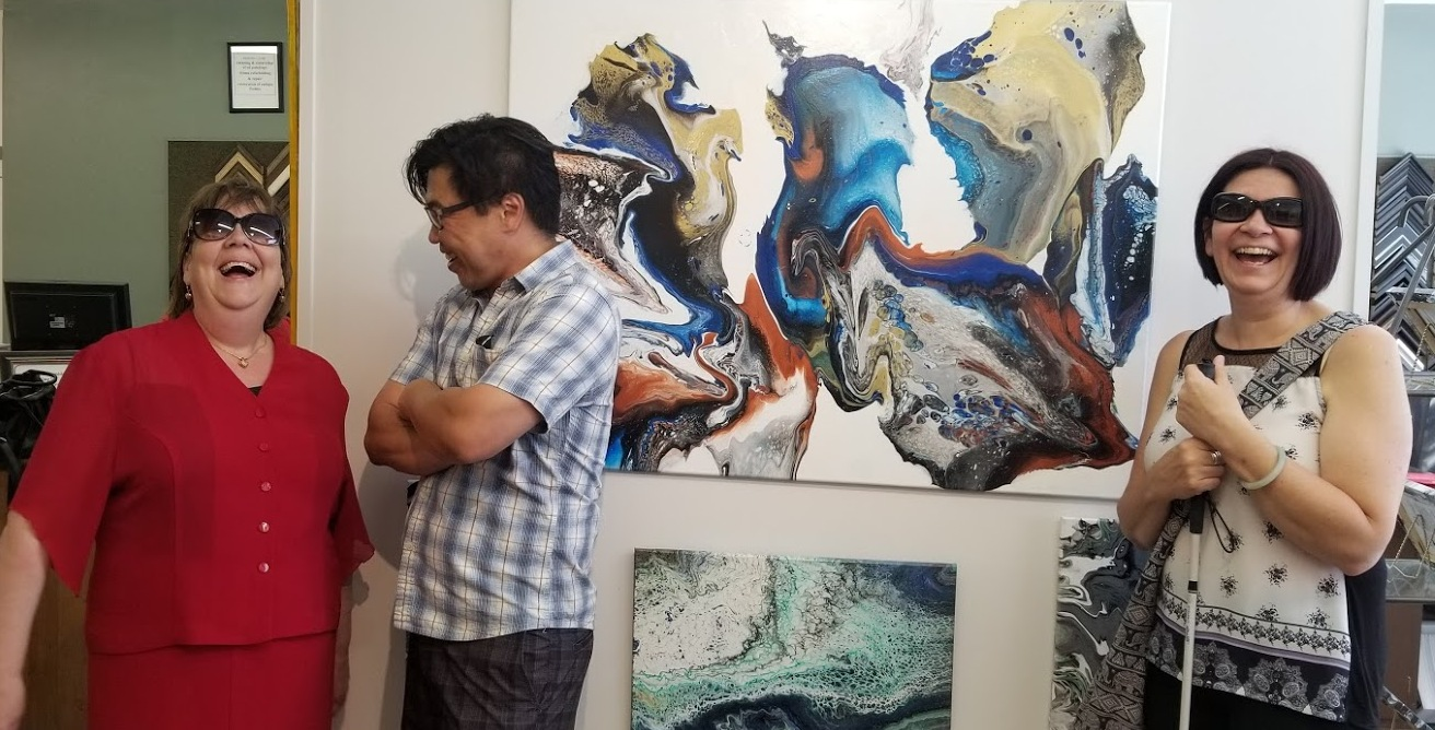 A man and two women standing in front of a large acrylic painting of a dragon